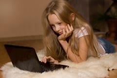 La niña está mirando la computadora portátil Imagen de archivo