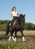 la niña está montando un caballo Foto de archivo libre de regalías