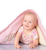 La niña está ocultando bajo la manta sobre el backgroun blanco Imagen de archivo