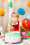 La niña está pensando en el deseo en su cumpleaños foto de archivo libre de regalías