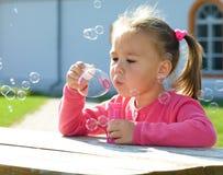 La niña está soplando burbujas de jabón Imágenes de archivo libres de regalías