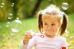 La niña está soplando burbujas de un jabón imagen de archivo
