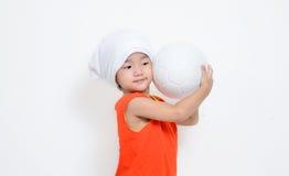 La niña está sosteniendo la bola al lado de su mejilla foto de archivo libre de regalías