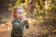 La niña está sosteniendo una ramita floreciente en la primavera fotos de archivo libres de regalías