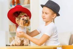 La niña está vistiendo su perro para arriba Imagen de archivo libre de regalías