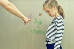 La niña estropeó el papel pintado Imagen de archivo libre de regalías