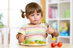 La niña examina las coles de Bruselas Niño con la comida sana que se sienta en la tabla en cuarto de niños Foto de archivo libre de regalías