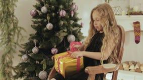 La niña feliz abre un regalo mágico de la Navidad por la chimenea por el Año Nuevo metrajes