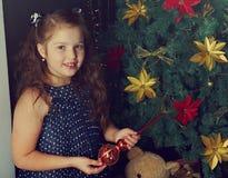 La niña feliz adorna el árbol de navidad Fotografía de archivo