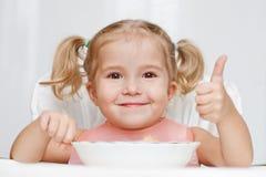 La niña feliz come con una cuchara mientras que se sienta en la tabla Imágenes de archivo libres de regalías