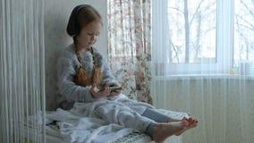 La niña feliz con las coletas en miradas de los auriculares en el vídeo del teléfono, se sienta en un cuarto en el alféizar, ocul metrajes