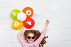 La niña feliz con las gafas de sol, sosteniendo el arco iris hincha Fotos de archivo libres de regalías
