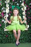 La niña feliz con los tréboles en la cabeza en verde se sienta en el oscilación Foto de archivo