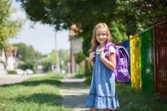 La niña feliz con una mochila va a la escuela Foto de archivo