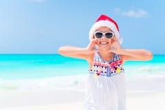 La niña feliz en el sombrero de Papá Noel durante vacaciones de la playa de la Navidad se divierte mucho Fotografía de archivo