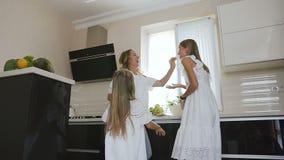 La niña feliz en el vestido blanco con su hermana y la mamá están bailando y escuchan música mientras que cocina la consumición e almacen de video