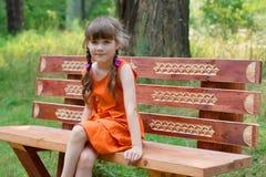 La niña feliz en naranja se sienta en beanch de madera en el verano Imagen de archivo