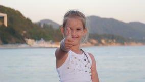 La niña feliz en la playa, niña muestra el gesto estupendo La mano de la muchacha con el pulgar encima del símbolo perfecto está  almacen de video