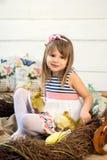 La niña feliz en un vestido con las flores en su cabeza se sienta en una jerarquía y sostiene los anadones mullidos lindos de Pas fotos de archivo