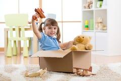 La niña feliz juega al piloto que se sienta en la caja de cartón en plano fotografía de archivo libre de regalías