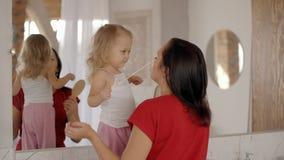 La niña feliz linda se está colocando cerca del espejo con la madre joven alegre almacen de video