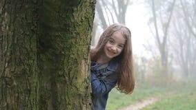 La niña feliz mira de detrás árbol y sonríe a la cámara almacen de video
