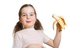 La niña feliz mordida de plátano Imagenes de archivo