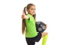 La niña feliz muestra los pulgares para arriba con el balón de fútbol en manos Imagen de archivo