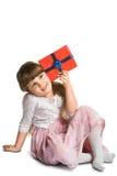 La niña feliz puso la caja de regalo al oído Fotografía de archivo
