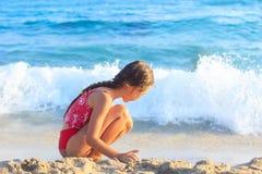 La niña feliz que juega con la arena por el mar agita Verano Su Imagenes de archivo