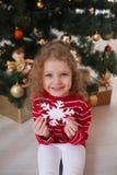 La niña feliz se sienta debajo del árbol de navidad y sostiene un copo de nieve Imagen de archivo libre de regalías