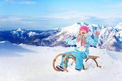 La niña feliz se sienta en el trineo en montañas Fotografía de archivo libre de regalías