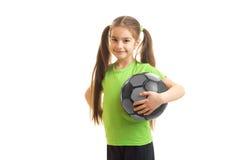 La niña feliz sonríe con el balón de fútbol en manos Fotografía de archivo