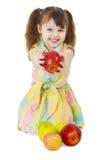 La niña feliz sonriente da una manzana Foto de archivo libre de regalías