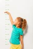 La niña finge cómo el alto ella está en escala de la pared fotos de archivo libres de regalías