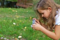 La niña fotografía una flor Imágenes de archivo libres de regalías