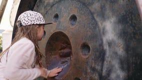 La niña frota el gongo redondo del metal para hacer un sonido almacen de video