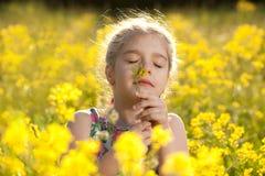 La niña goza del olor de flores Foto de archivo libre de regalías