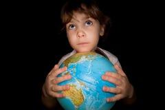 La niña guarda adentro entrega el globo del mundo Foto de archivo