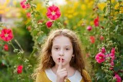 La niña guarda el finger delantero en los labios pide silencio Fotografía de archivo libre de regalías
