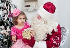 La niña habla con Santa Claus Fotos de archivo