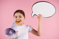 La niña habla en el megáfono que lleva a cabo discurso fotografía de archivo