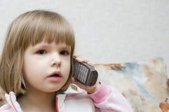 La niña habla por el teléfono Foto de archivo libre de regalías