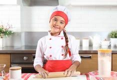 La niña hace la pasta en cocina con el rodillo foto de archivo