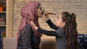 La niña hace un compensar a su madre musulmán en el hijab, cepillo del maquillaje, riendo, familia sonriente, idilio, comodidad c almacen de video