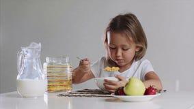 La niña hambrienta fastly está comiendo los copos de maíz con leche almacen de metraje de vídeo