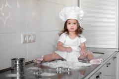 La niña hermosa aprende cocinar una comida en la cocina fotos de archivo