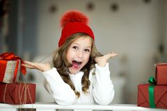 La niña hermosa celebra la Navidad Días de fiesta del ` s del Año Nuevo Muchacha feliz en un traje de la Navidad con el regalo Imagenes de archivo