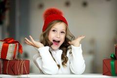 La niña hermosa celebra la Navidad Días de fiesta del ` s del Año Nuevo Muchacha feliz en un traje de la Navidad con el regalo Imágenes de archivo libres de regalías