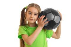 La niña hermosa con el balón de fútbol gris en sus manos mira la cámara Fotos de archivo libres de regalías